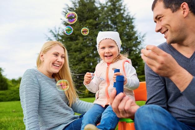 Famiglia che gioca con le bolle all'aperto