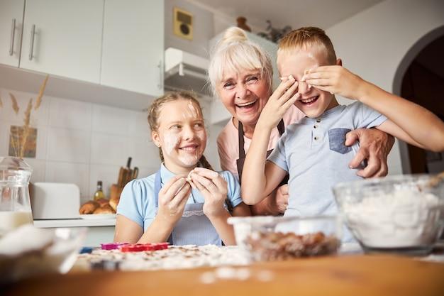 Ritratto di famiglia della nonna e dei nipoti durante la preparazione dei biscotti