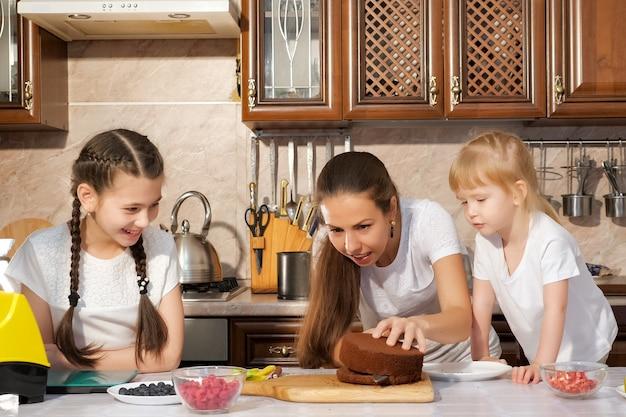 Ritratto di famiglia di mamma e figlie stanno preparando la torta di compleanno insieme, la mamma sta tagliando il pan di spagna usando il coltello in cucina.