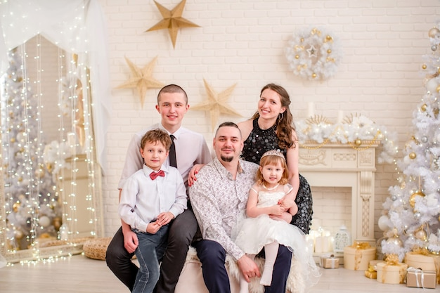 Ritratto di famiglia in studio decorato per il nuovo anno. serata di natale in famiglia. famiglia per riunirsi abbracciando e sorridendo. soggiorno decorato con camino e albero di natale