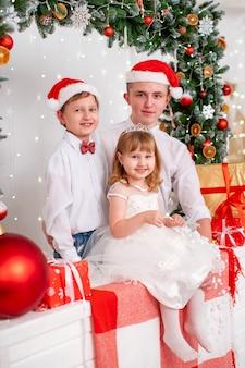 Ritratto di famiglia in studio decorato per il nuovo anno. foto di famiglia di natale per la memoria. bambini sorridenti fratelli e sorelle. ghirlanda di conifere decorata con giocattoli natalizi.