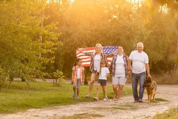 Famiglia che propone all'aperto con la bandiera americana