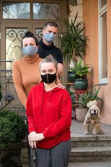 Famiglia che posa in maschere protettive all'aperto per prevenire coronavirus, covid-19, germi, fumi tossici e polvere