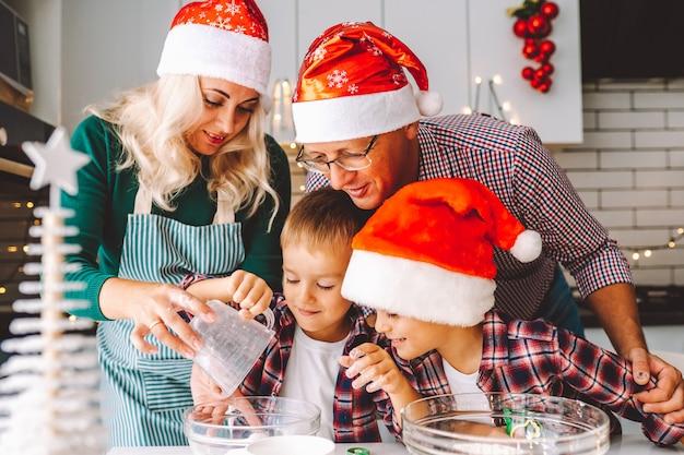 Famiglia che prepara i biscotti per la vigilia di natale