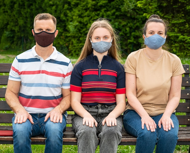 Famiglia in maschere protettive che si siede su una panchina nel parco