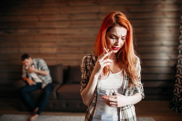 Litigio familiare, moglie che fuma sigaretta, stress, coppia in conflitto. relazione problematica