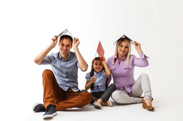 Famiglia che legge un libro insieme sdraiata sul pavimento a casa