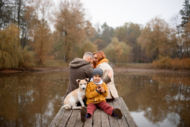 Famiglia che si rilassa all'interno e che segna il cane di animale domestico