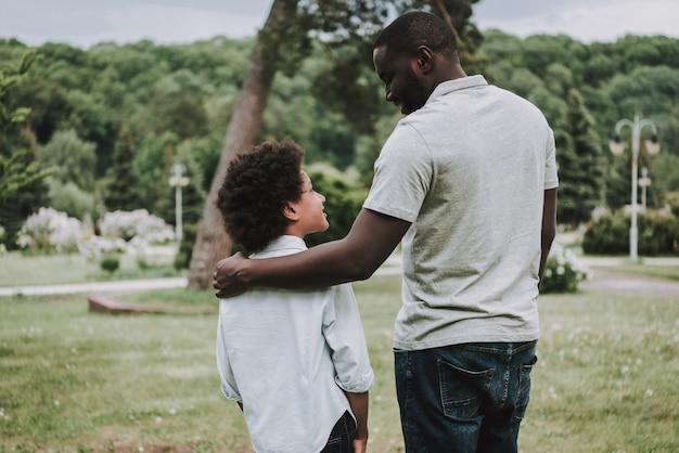 Famiglia che riposa nel parco e nel padre che osservano figlio.