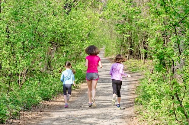 Famiglia in esecuzione felice madre attiva e bambini che fanno jogging all'aperto corrono con i bambini nella foresta