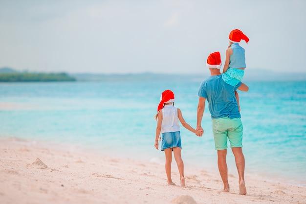 Famiglia in cappelli di babbo natale su una spiaggia tropicale che celebra le vacanze di natale