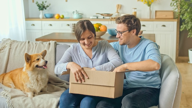 La famiglia soddisfatta da una consegna rapida. disimballaggio dell'ordine dai negozi online. happy family apre il pacco ricevuto in una grande scatola di cartone. acquisti di famiglia insieme.