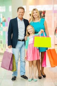 Famiglia nel centro commerciale. tutta la lunghezza della famiglia allegra che tiene le borse della spesa e sorride mentre si trova in un centro commerciale