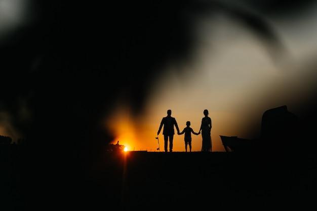 Siluette della famiglia con il bambino al tramonto papà tiene lo skateboard