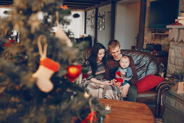 Famiglia seduta sul divano con albero di natale fuori fuoco in fronte