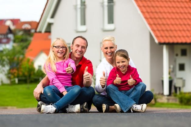 Famiglia seduto di fronte a casa