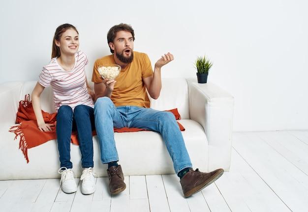 La famiglia seduta a casa sul divano riposa a guardare l'intrattenimento televisivo