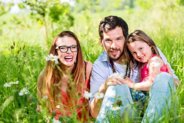 Famiglia che si siede sul prato che dà loro protezione del bambino