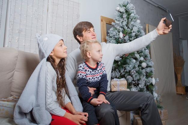 Famiglia seduta vicino all'albero di natale e fare selfie