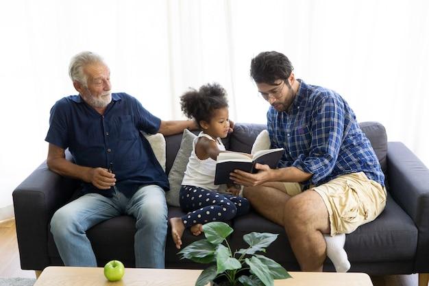 Famiglia seduta sul divano a leggere un libro e guardare la tv