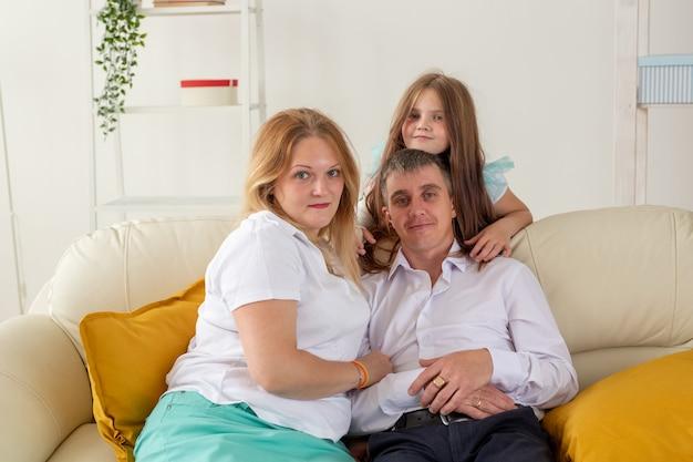 La famiglia seduta sul divano nel soggiorno della figlia ha una mano ferita ma è felice di stare insieme