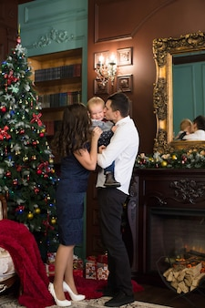 Famiglia seduta insieme in un interno di natale. la famiglia felice si diverte con i regali di natale. ritratto di famiglia di natale, madre, padre e figlio celebrano l'occasione.