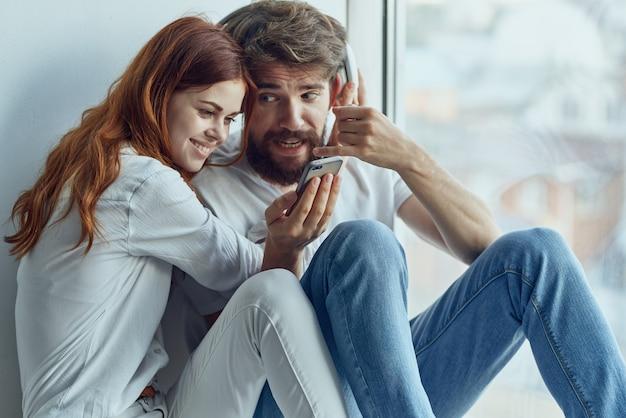 Famiglia seduta sul davanzale della finestra romanticismo gioia tecnologia