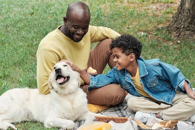 Famiglia seduta con cane all'aperto
