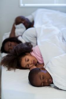 Famiglia che dorme sul letto