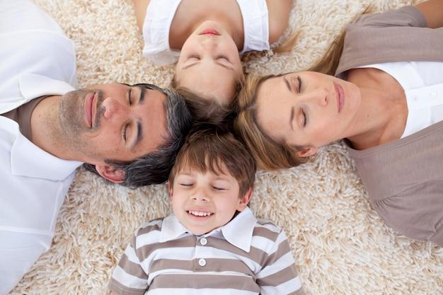Famiglia che dorme sul pavimento con le teste insieme