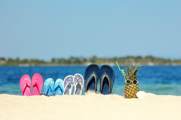 Pantofole per famiglie sulla sabbia in spiaggia in estate