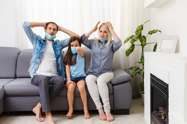 Famiglia sul divano guardare la tv a casa. resta a casa durante la quarantena