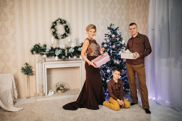 Famiglia e figlio pongono vicino all'albero di natale con i regali nelle loro mani