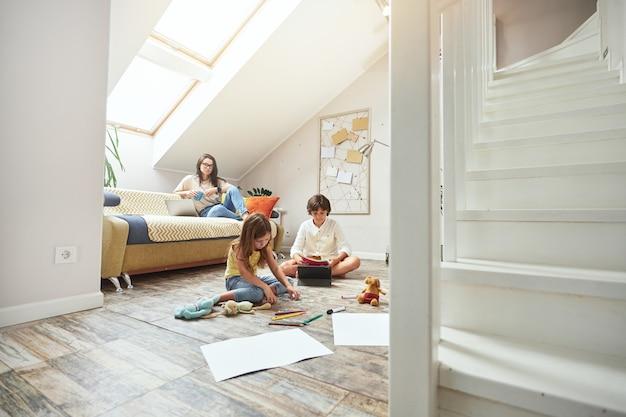 La famiglia trascorre del tempo insieme a casa i bambini seduti sul pavimento e giocando mentre la madre con