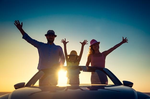 Famiglia in piedi su un'auto sullo sfondo del cielo al tramonto