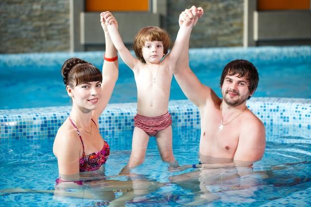Famiglia che nuota in piscina.