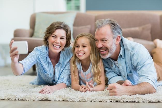 Famiglia che cattura selfie dal telefono cellulare mentre giaceva insieme sul tappeto nel soggiorno