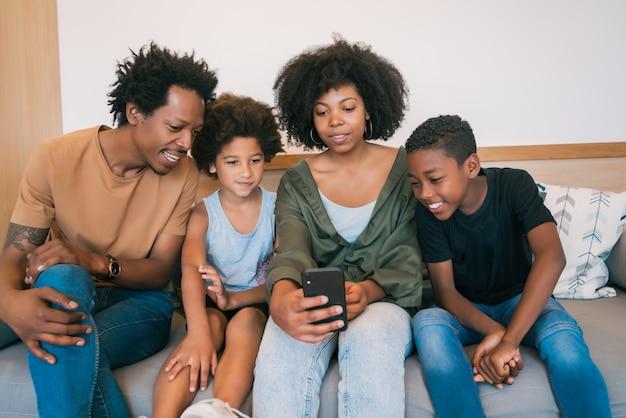 Famiglia che prende selfie insieme al telefono a casa.