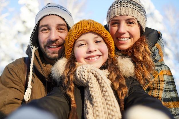Famiglia che prende selfie in inverno