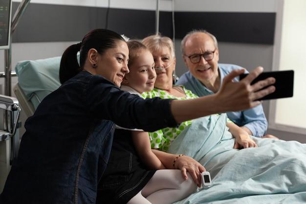 Famiglia che prende selfie con la nonna in pensione malata durante il ricovero medico