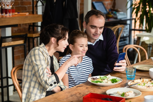 Una famiglia di tre persone a un tavolo da pranzo prendendo un selfie