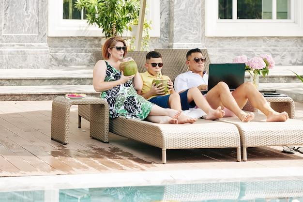 Famiglia di tre persone che si godono le vacanze estive, bevono cocktail al cocco e prendono il sole sulle sedie a sdraio a bordo piscina