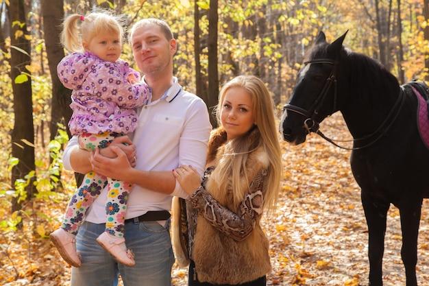 Famiglia di tre persone con un cavallo per una passeggiata nella foresta autunnale