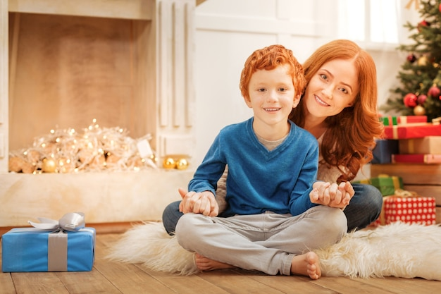 Legami familiari. famiglia allegra che si siede sul pavimento mentre si tengono le mani insieme a casa.