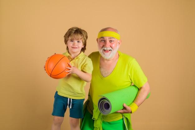 Tempo in famiglia insieme. sport di famiglia. ritratto di un nonno sano e di un figlio che si allenano. tempo per la famiglia. nonno e bambino sportivo. vecchio con tappeto yaga. pallacanestro. yoga. sportivo. gioco sportivo.