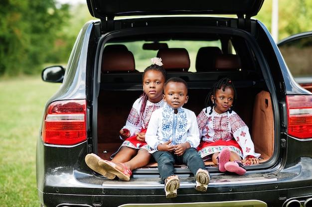 La famiglia in abiti tradizionali sta contro la macchina, i bambini si siedono sul bagagliaio