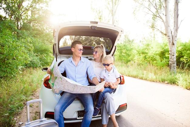 Famiglia, trasporto, sicurezza, viaggio su strada e concetto di persone - felice uomo e donna con bambino piccolo viaggio.