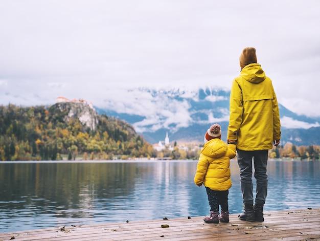 Famiglia viaggi europa madre e bambino in impermeabili gialli guardando il lago di bled slovenia