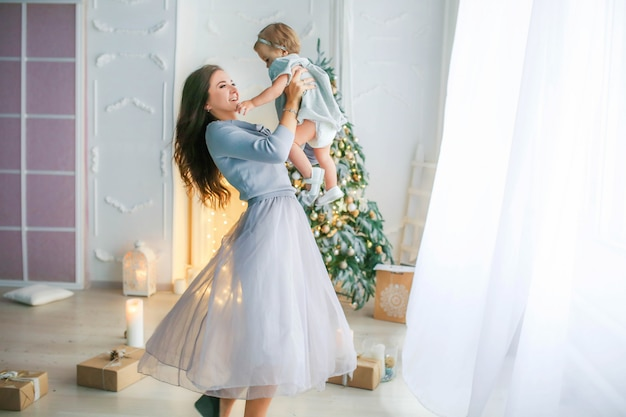 Famiglia di due persone madre e figlia di 1 anno sullo sfondo della foto dell'albero di natale in colori vivaci.