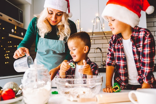 Famiglia di due ragazzi gemelli e madre che prepara i biscotti per natale in cucina indossando cappelli di babbo natale.